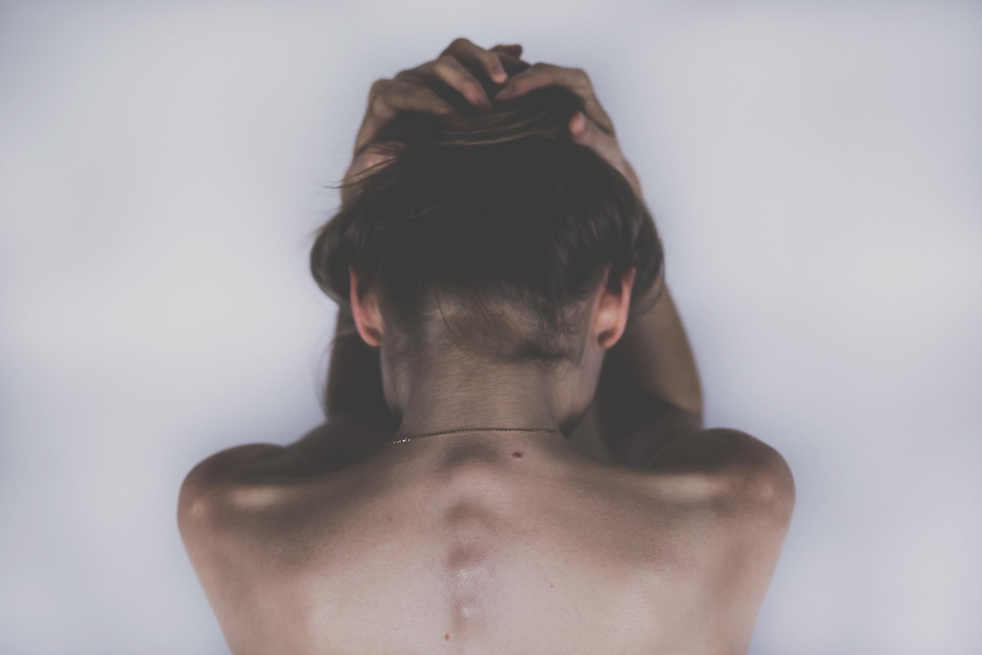woman holding head due to headache