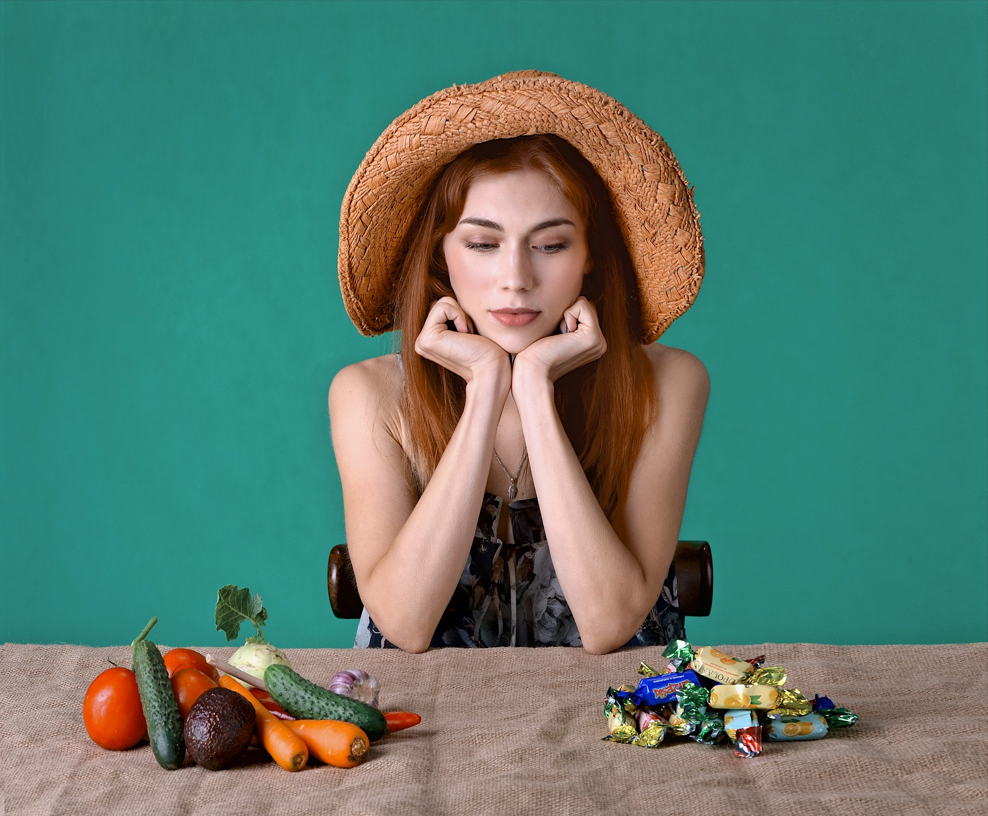 woman choosing between vegetables and candy