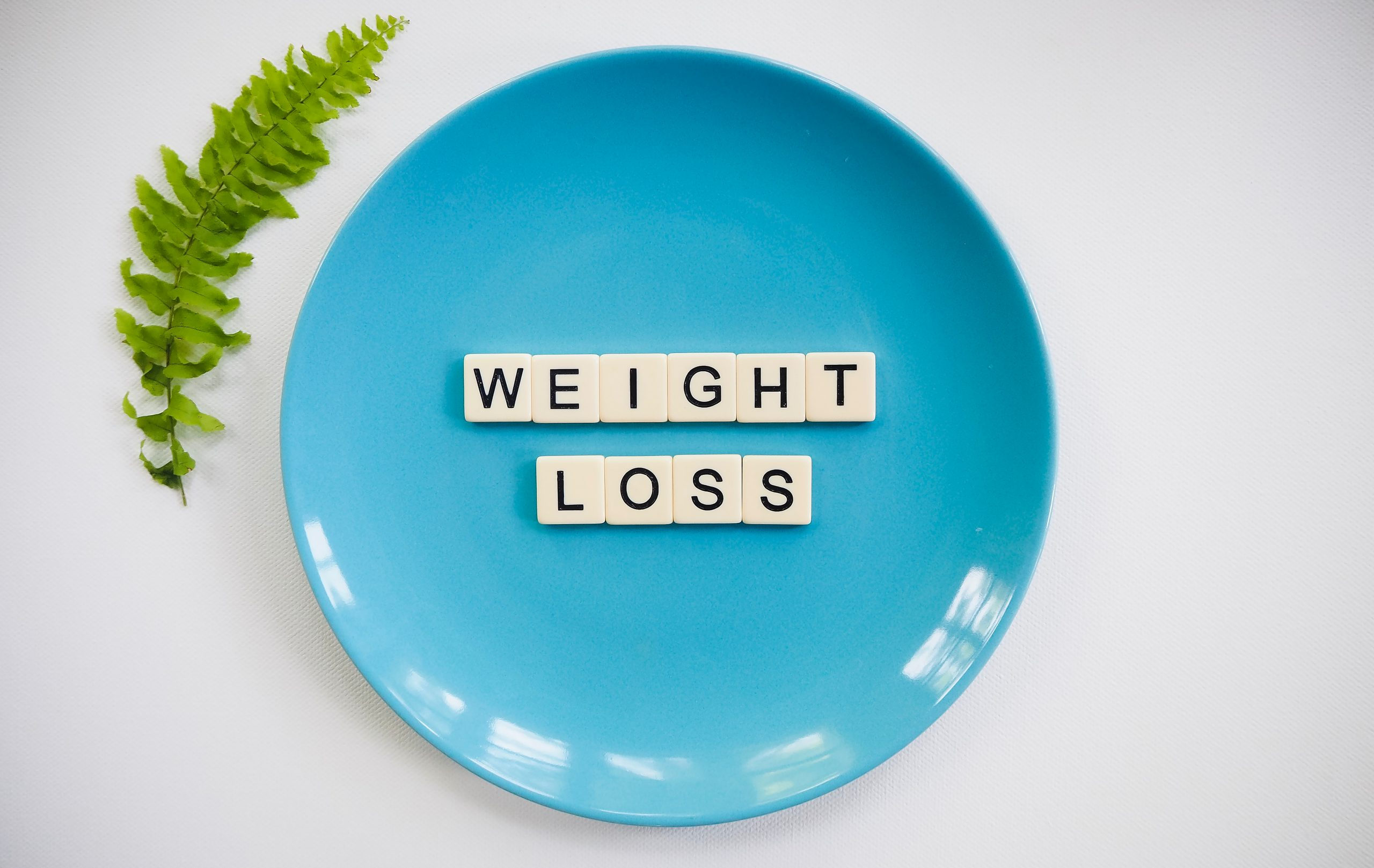 scrabble tiles spelling weight loss on a plate